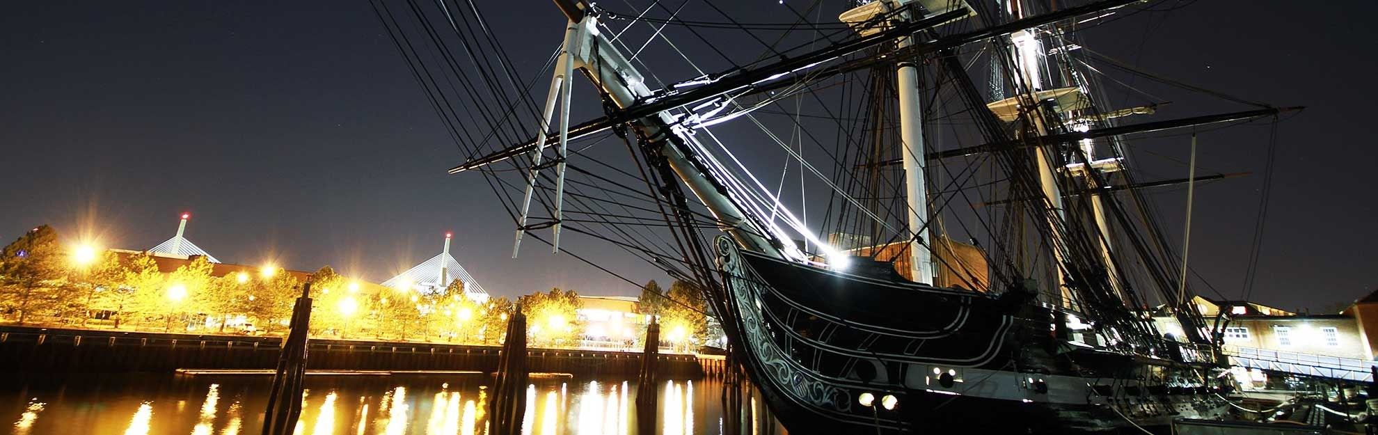 USS Constitution at the Boston harbour quay at night.